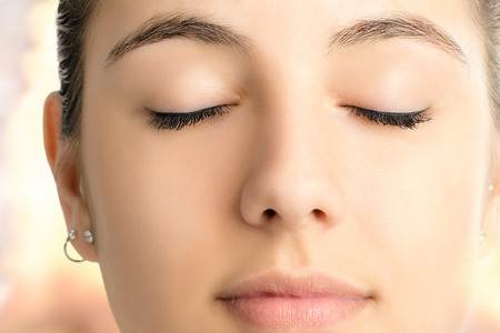 esoterismo: Extreme close up face shot of attractive young woman meditating with eyes closed against colorful bright background.