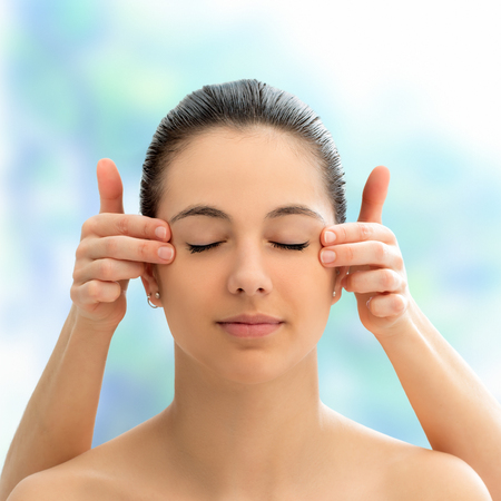 Close up face shot of young woman at alternative medicine session.Therapist touching side of woman�s head. Stock Photo