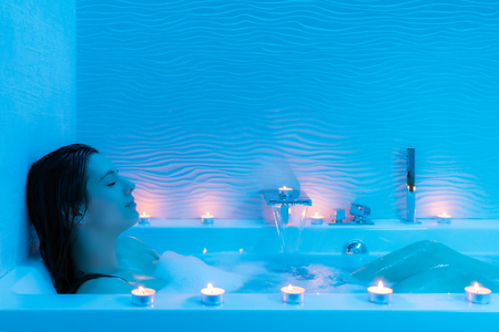 Close up portrait of young woman relaxing in hot foam bath at home.Low key blue ambient with decorative candles along bath tub.