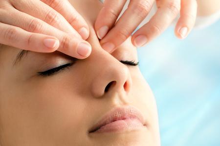Extreme close-up van de therapeut doen reiki op jonge vrouw. Vingers uitoefenen van druk tussen de ogen.