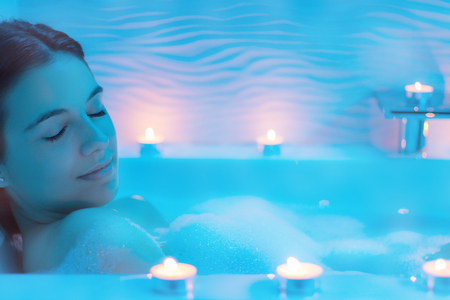 Close up  Low light ambient portrait of woman enjoying foam bath.Blue ambient with decorative candles along bath tub.