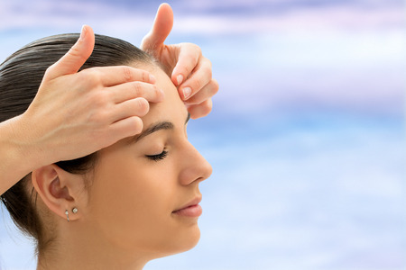Therapist doing alternative healing on young woman. Reiki therapist touching energetic area on forehead. 스톡 콘텐츠
