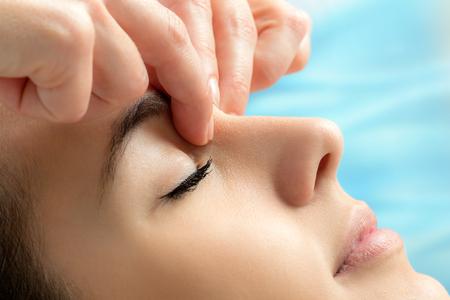 Extrema cerca de las manos de aplicar la presión entre los ojos en la joven woman.Therapist aliviar la tensión emocional tocar las zonas sensibles en la cara. Foto de archivo