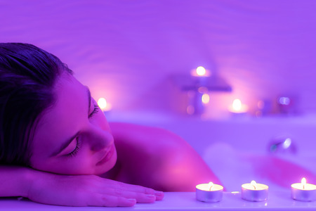 sensual massage: Close up Low light portrait of young woman relaxing in foam bath.Low colorful candlelight ambient with candles on bath tub.