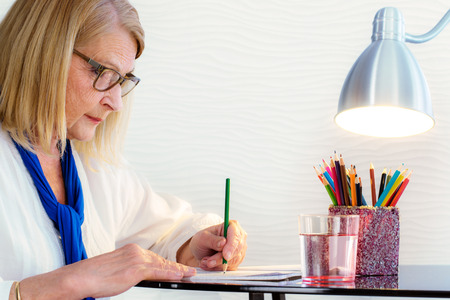 Close-up portret van senior vrouw met kunsttherapie met kleurboek voor volwassenen thuis.