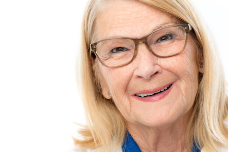 Close up face shot of attractive senior woman with charming smile.Blond lady wearing glasses isolated on white background. Stock Photo