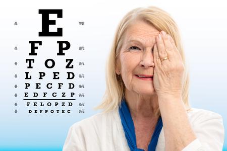 백그라운드에서 테스트 차트와 비전을 테스트하는 수석 여자의 초상화를 닫습니다. 손으로 한쪽 눈을 감고입니다.