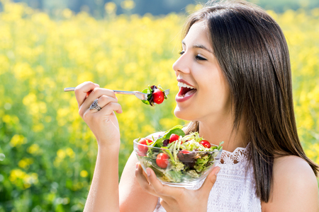 close up: Close up face shot of attractive healthy girl eating salad outdoors with flower field in background.