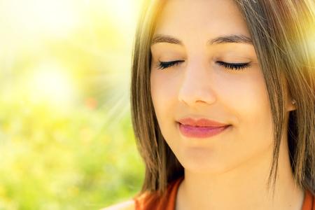 Close up retrato de atractiva mujer joven relajada meditating outdoors.Girl con los ojos cerrados contra el fondo colorido al aire libre brillante. Foto de archivo - 77400244