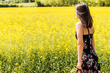 fullness: Close up portrait of young woman next to yellow flower field.Girl in black flower dress giving back. Stock Photo