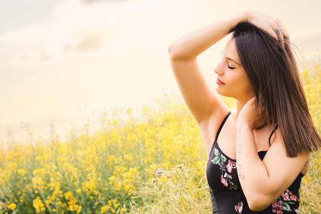 Close up portrait of attractive woman relaxing with eyes closed in yellow flower field. Imagens
