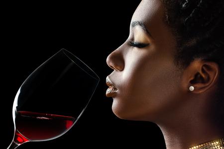 Macro dicht omhoog rustig portret van sensuele Afrikaanse vrouw die rode wijn ruikt. Achtermening van meisje met rode wijnglas naast gezicht tegen zwarte achtergrond. Stockfoto