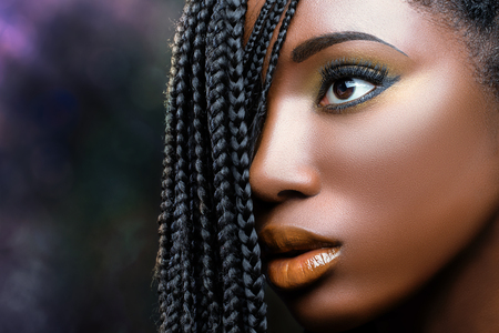 Macro close up african beauty face shot of young woman with braids. Professional make up fantasy portrait of attractive girl.