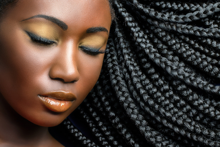 Extreme close up beauty cosmetic portrait of young african woman  with eyes closed.Girl wearing professional make up showing black braided hairstyle.