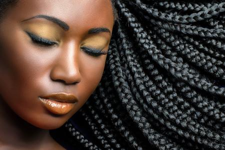 Extreme close-up schoonheid cosmetisch portret van jonge Afrikaanse vrouw met gesloten ogen. Glimlachende professionele make-up met zwart gevlochten kapsel.