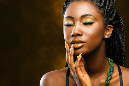 Close up studio portrait of attractive young african woman with long braided hair.Girl with eyes closed touching face with hand.