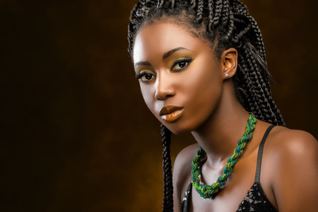 Close up Studio portrait of beautiful young african woman with braids. Low key face shot of elegant girl looking at camera against dark background.