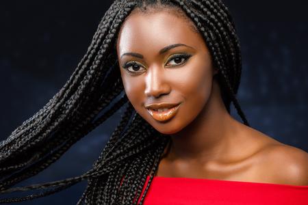 Sluit omhoog studiongezicht van het charmante jonge Afrikaanse meisje met gevlecht kapsel dat wordt geschoten.
