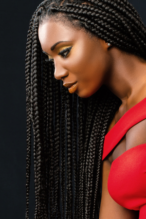 Close up vertical beauty portrait of young african woman with long braided hair against dark background.