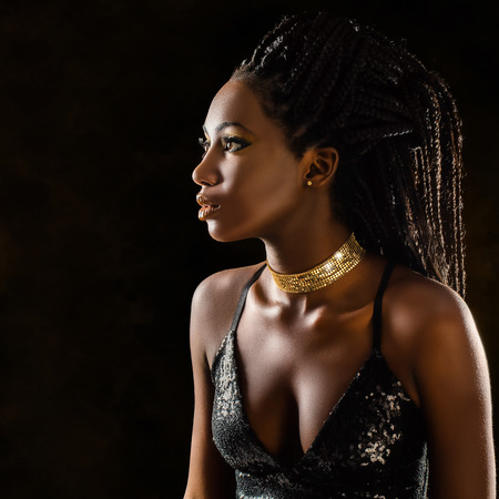 Close up portrait of elegant young african woman in party dress. Low key close up studio shot of girl with long braided hair against dark background.