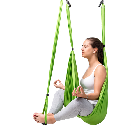 body scape: Portrait of young woman doing aerial yoga. Girl sitting with eyes closed in green anti gravity yoga hammock isolated on white background. Stock Photo