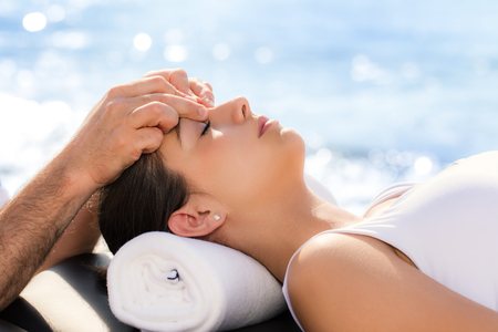 energy healing: Close up of portrait of young woman at osteopathic treatment session outdoors.Therapist applying pressure between eyes.