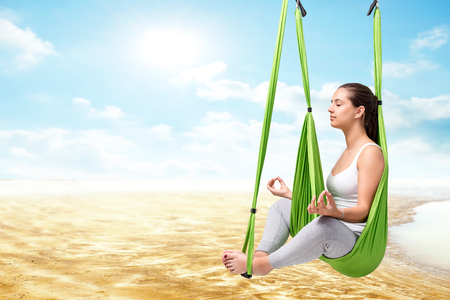 body scape: Conceptual portrait of young woman sitting in anti gravity yoga hammock with eyes closed.Girl doing spiritual exercise against river bed and blue sky.