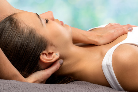 Close up detail of therapist doing osteopathic neck treatment on woman against colorful background. Stock Photo