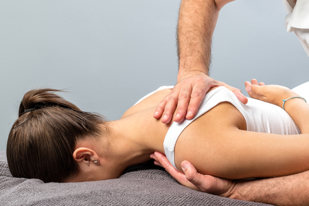 Close up detail of mail physiotherapist applying pressure on female shoulder blade.