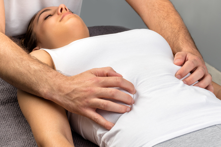alternative practitioner: Close up of hands doing physical osteopathic thorax massage on young woman.