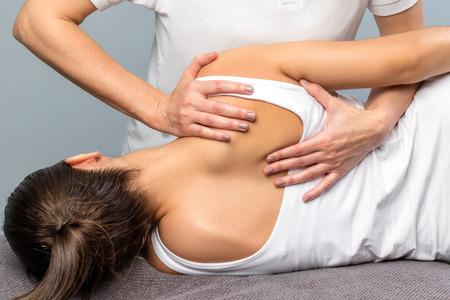 Sluit omhoog van detail van vrouwelijke fysiotherapeut die schouderbladbehandeling op patiënt doen. Stockfoto