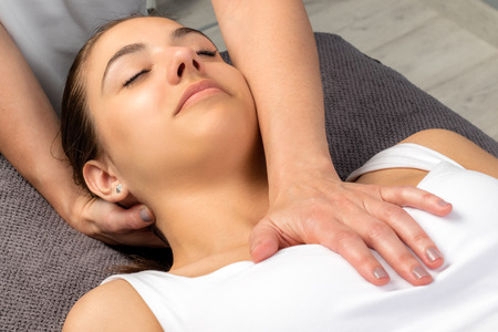 Close up top view of young woman receiving physical neck and chest treatment.