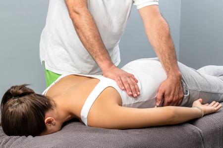 Close up of male osteopath doing manipulative massage on female lower back. Stock Photo