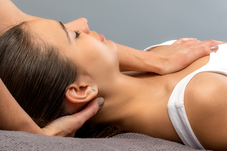 Detail of young woman at osteopathic treatment session. Therapist manipulating neck and chest of patient.