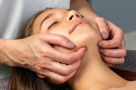 repose: Extreme close up of therapist applying pressure under little girl's chin. Stock Photo