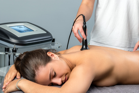 alternative practitioner: Close up of young woman receiving interferential electrotherapy.Therapist stimulating nerve on spine with apparatus. Stock Photo