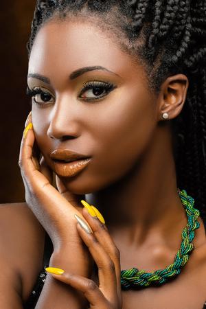 魅力的な若いアフリカ女性のスタジオ ポートレートを閉じます。次の顔に女の子手の美しさのショット