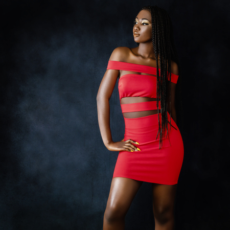 Close up portrait of sensual young african woman in red dress.Studio shot of girl  with long braided hair against fringe background. Stock Photo