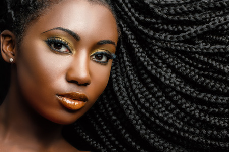 Extreme close up beauty portrait of young african woman showing long braided hair next to face. Reklamní fotografie - 81161375