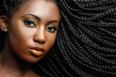 Extreme Nahaufnahme Schönheit Porträt der jungen afrikanischen Frau zeigt lange geflochtene Haare neben dem Gesicht.