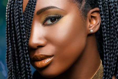 Extreme close up facial beauty portrait of  young charming african girl with braided hairstyle.Studio shot of woman with professional make up looking at camera. Standard-Bild