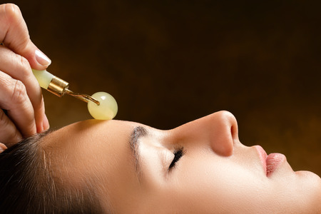 Macro close up side view of woman having beauty treatment in spa.Therapist applying jade roller on forehead. Stock Photo
