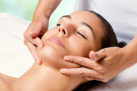 Close up facial massage on female chin.Therapist applying revitalizing cream on face.