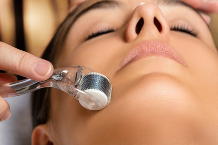 Macro close up portrait of woman having beauty skin tightening treatment.Therapist rolling with derma skin roller on female face. Stockfoto