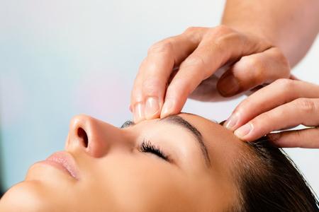Close up portrait of woman enjoying beauty treatment. Therapist hands massaging forehead.