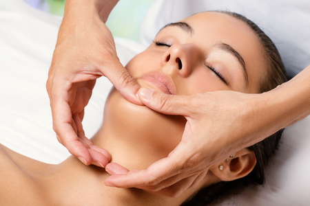 Close up of woman having facial beauty treatment in spa. Therapist applying revitalizing cosmetic product on chin. Stock Photo