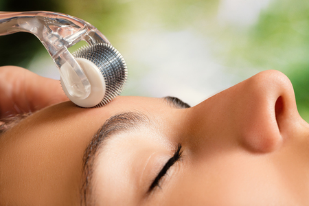 Macro close up portrait of woman having beauty skin treatment.Therapist preparing skin with derma roller.