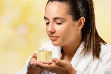 エッセンシャル オイルの香りを臭いがする白スパ ガウンの女性の肖像画を閉じます。アロマの香りで小さなボトルを保持している少女。 写真素材