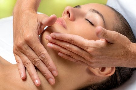repose: Close up portrait of woman having facial treatment in spa.Hands applying neck cream with continuous smooth movements on woman.