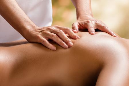 Sluit omhoog detail van handen die fysiotherapie op vrouwelijke stekel doen tegen kleurrijke achtergrond. Stockfoto
